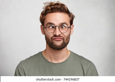 Funny comic man crosses eyes, pouts lips, makes grimace, foolishes after all day studying. Clueless male nerd with awkward expression has fun alone, plays fool, isolated over white background