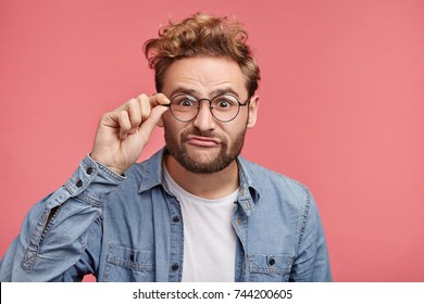 Funny comic young male with beard pouts lips, makes grimace looks through glass spectacles, wears casual clothes, isolated over pink background. Awkward male student wonk with joyful expression