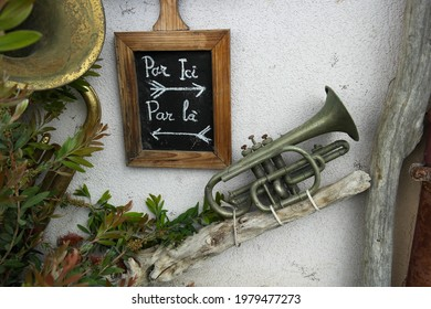 """Funny composition on a wall with an old trumpet and a slate marked with two opposite directions written in French.. Translation """"par ici, par là"""" :  over here, over there  - Shutterstock ID 1979477273"""