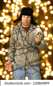 Funny confused man wrapped in colorful Christmas lights