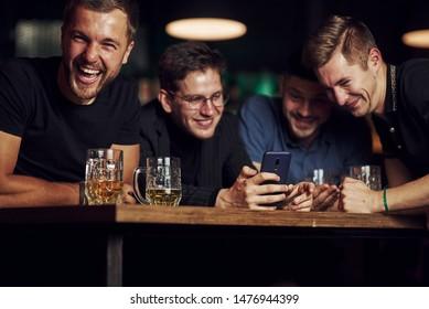 Hübsche Inhalte auf dem Smartphone. Drei Freunde ruhen in der Kneipe mit Bier in Händen. Unterhaltung.
