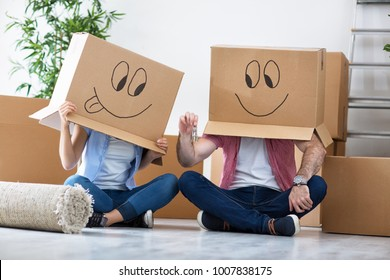Funny couple celebrating move to new apartment, enjoy at new home between boxes