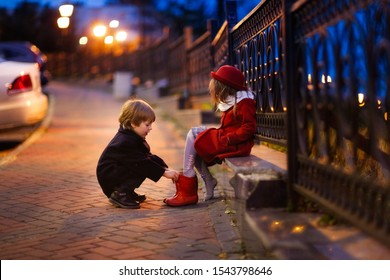 funny couple of children in the evening in the park, a boy helps a girl to shoe boots, a girl in a red coat and hat. Valentine's day concept, baby love and care