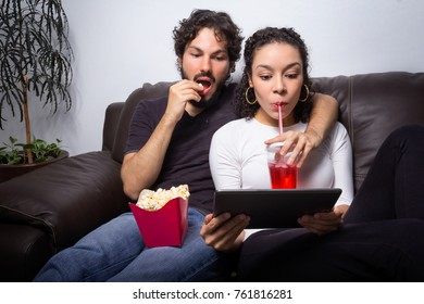 Funny couple is drinking soda and eating popcorn. Watching videos, movies and series online. Sitting on the sofa at home. Leisure at home, entertainment industry. Hanging out, bonding and relaxing.