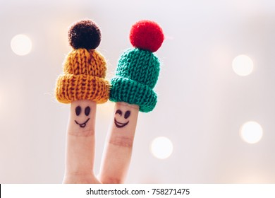 Funny couple fingers on knitted winter warm hats smiling and wink