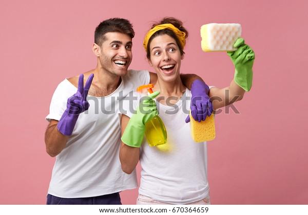 Pareja divertida divirtiéndose durante las tareas domésticas y la limpieza: un hombre sonriente abrazando a su esposa que se hace selfie con esponja. Hombres y mujeres alegres usando esponjas como selfie para smartphones