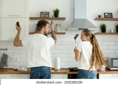 Funny couple having fun enjoying cooking in kitchen together, young man and woman preparing food feeling happy and playful helping standing their back to camera holding knife and spatula, rear view