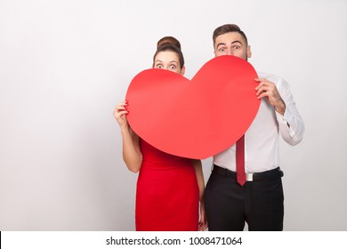 Funny couple hide and seek behind big red heart. Indoor, studio shot, isolated on gray background
