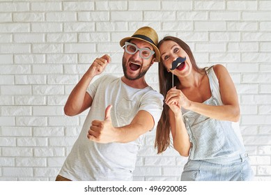 Funny couple holding paper moustache and glasses, they are laughing