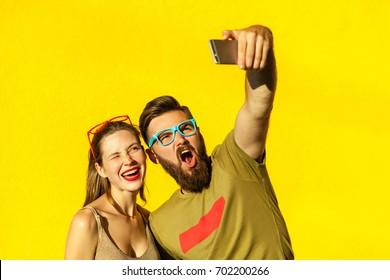 funny couple making selfie on yellow background. Studio shot