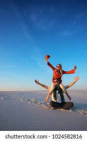 Funny couple, man with a laughing girl on his shoulders sits in the desert on a sunny evening, fools around and having fun. Happy people get new impressions and enjoy life during travel and tourism.