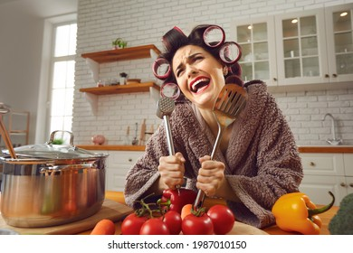 Funny crazy cheerful woman housewife in curlers and furry bathrobe standing in kitchen and holding kitchenware in hands during cooking. Funny women at home concept