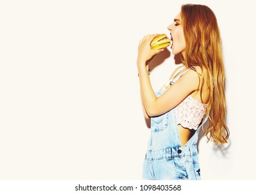 Funny crazy glamor stylish sexy smiling beautiful young blond woman model in summer bright hipster jeans clothes eating hamburger