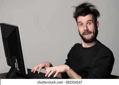 Funny and crazy man using a computer on gray background. man's hands on the keyboard