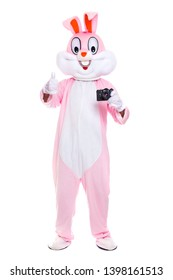 Funny crazy photorapher with camera shoots easter party. Life size easter bunny holds photocamera, takes a pictures on white background