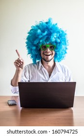 funny crazy young man with blue wig using notebook on the table