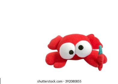 A funny crazy-eyed toy crab with a carrot isolated on white