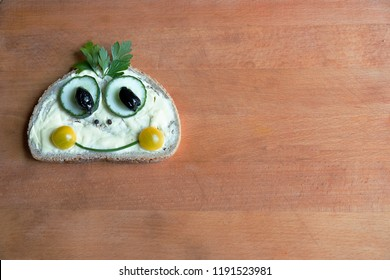 The funny creative little face on a butter sandwich consisting of tomato halves. cucumber. butter and parsley on the wooden board.Assemblage style