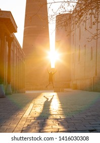 funny creative young girl in denim hipster clothes jumping up against sun rays making big shadow.
