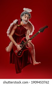 Funny Cupid emotionally sings and dances with an electric guitar. Contemporary rock musician Amur. God of Love. Valentine's Day and Love. Studio portrait on a red background.