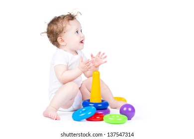 Funny curly baby playing with a plastic pyramid