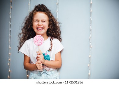Funny curly girl with lollypop on grey background with lights.