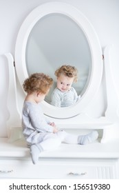 Funny cute baby girl watching her reflection in a white bedroom with a beautiful round mirror