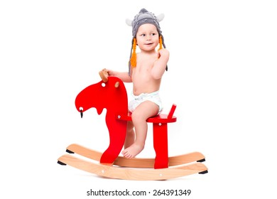 Funny cute baby sitting on the toy horse or elk in Asterix hat, smiling isolated on white