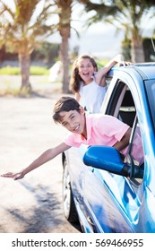 Funny and cute boy and girl in the car on nature background