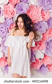 Funny cute brunette girl wearing white dress off the shoulder stands in a studio with pink flowers background. Girl is having fun and smiles widely. She wears white watch and plays with hair.