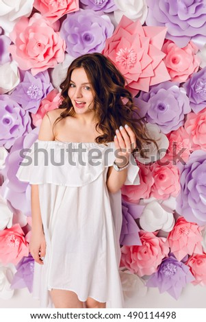 d0aba591b6d Funny cute brunette girl wearing white dress off the shoulder stands in a  studio with pink