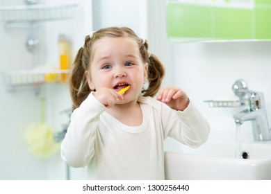 f212753e90 funny cute child girl brushing her teeth in bathroom