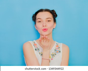 Funny cute girl on a blue studio background. Bright emotional female portrait. Woman sends air kiss playful