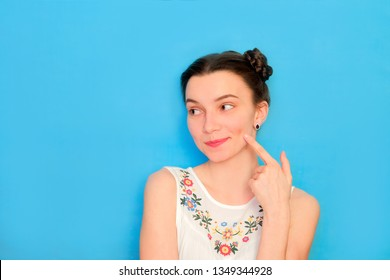 Funny cute girl on a blue studio background. Bright emotional female portrait. Shy woman flattered. Ask for cheek kiss.