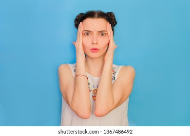 Funny cute girl on a blue studio background. Bright emotional female portrait. Woman touching head in shock.