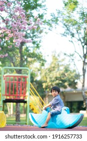 Funny cute happy baby playing rocking horse on the flower tree playground. The emotion of happiness