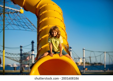 Funny cute kid playing in tunnel slide on playground.