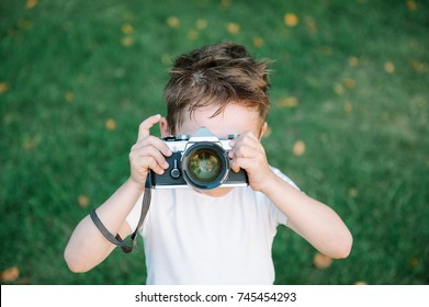 funny cute kid wants to take a picture with his vintage film camera on green grass backdrop with some fallen leaves