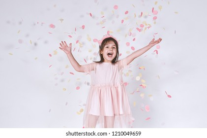 Funny cute little girl wearing pink dress in tulle with princess crown on head isolated on white background rise hands up enjoy confetti. Pretty little girl celebrating her birthday party, having fun