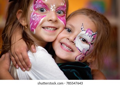 Funny cute little girls with painting faces are hugging ang having fun.