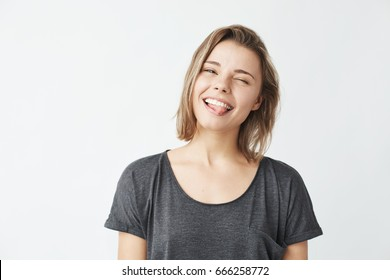 Funny cute young girl smiling winking showing tongue looking at camera over white background.
