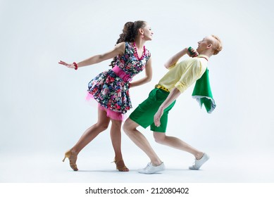 Funny dancer couple dressed in boogie-woogie rock'n'roll pin up style posing together in studio. Woman in yellow dress in black dots jokingly attack man in green shirt deviated from her.