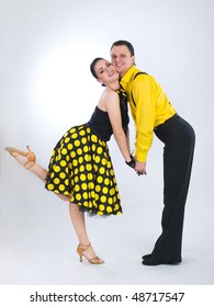funny dancers in yellow clothing over grey background