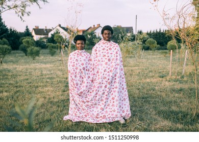 Funny dark skinned couple wrapped in sheet standing together outdoor in autumn park.