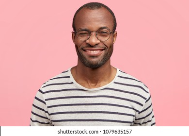 Funny dark skinned male blinks eye and has positive delighted expression, wears striped t shirt and round glasses, poses agaist pink background. People, ethnicity, happiness and positiveness concept