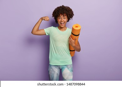 Funny dark skinned woman raises arm, shows muscles after training, holds karemat, has regular workout in gym with coach, dressed in sportswear, isolated on purple studio wall. Strength concept
