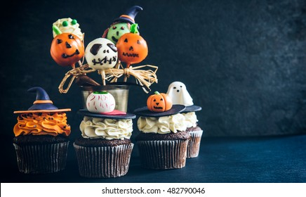 Funny delicious cake pops and cup cakes for Halloween on the table,selective focus and empty space