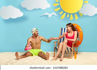 Funny delighted male vacationist sits on warm sand, carries inflated pink flamigo for swimming, wears goggles and shorts, keeps hand of girlfriend who sits on beach chair. Summer vacation concept