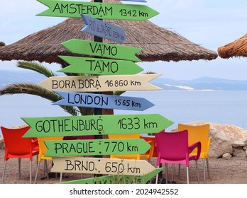 Funny direction signpost with distance to many different cities in the world