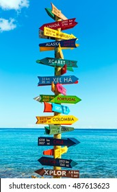 Funny direction signpost with distance to many different countries on Mexican coastline (Riviera maya)
